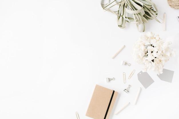 평면 위치, 최고보기 사무실 테이블 책상. 꼬기, 연필, 꽃 꽃다발, 공예 일기 및 흰색 배경에 클립과 여성 책상 작업 공간.