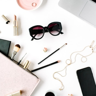 Плоская планировка, рама стола офисного стола вид сверху. женское рабочее пространство стола с ноутбуком, сцеплением, косметикой, телефоном, солнцезащитными очками, бутонами роз помады на белом фоне.