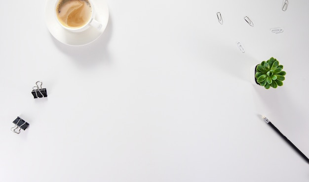 フラット横たわっていた、トップビューオフィステーブルデスク。空白のクリップボード、事務用品、鉛筆、緑の葉、コーヒーのあるワークスペース