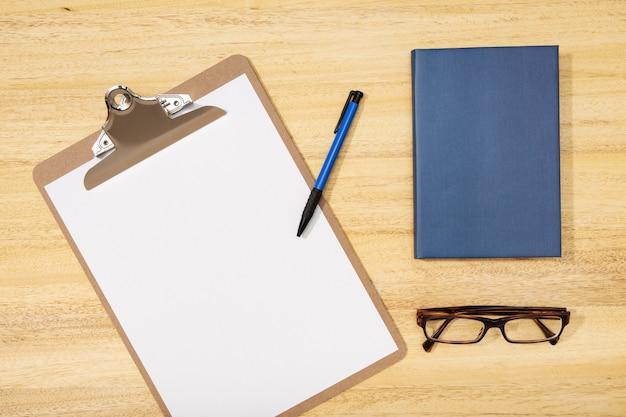 フラット横たわっていた、トップビューオフィステーブルデスク。空白のクリップボード、ペン、メガネ、木製のテーブルの日記とワークスペース