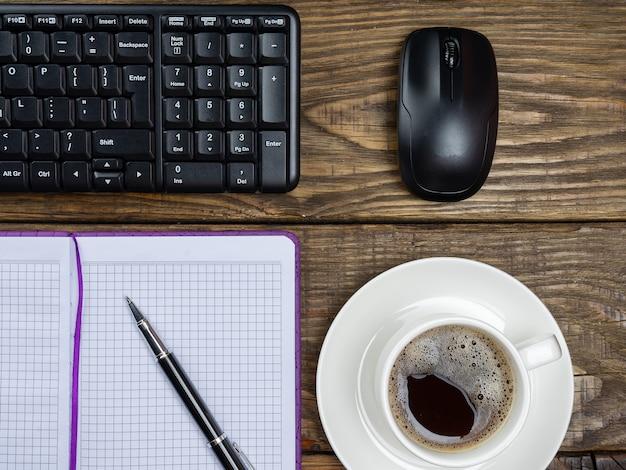 Плоская планировка, офисный стол, вид сверху. рабочее пространство с пустой записной книжкой, клавиатурой, канцелярскими принадлежностями и кофейной чашкой на деревянном фоне.