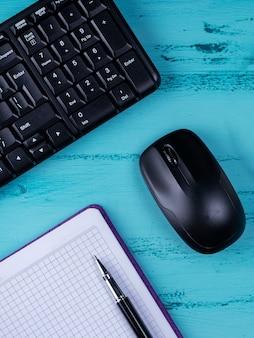 Плоская планировка, офисный стол, вид сверху. рабочее пространство с пустой записной книжкой, клавиатурой, канцелярскими принадлежностями, на деревянных фоне.
