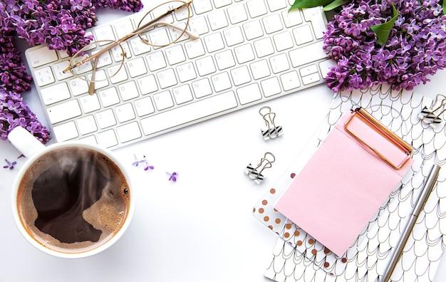 Плоская планировка, офисный стол, вид сверху. рабочее пространство с клавиатурой, сиреневыми цветами и канцелярскими товарами на белом фоне.
