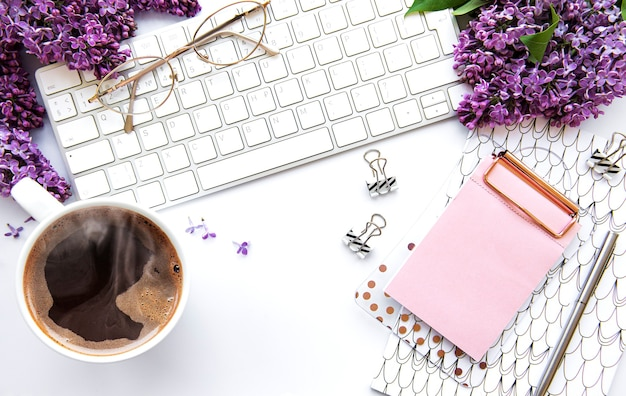 Flat lay, top view office table desk. workspace with keyboard, lilac flowers and office supplies  on white background.