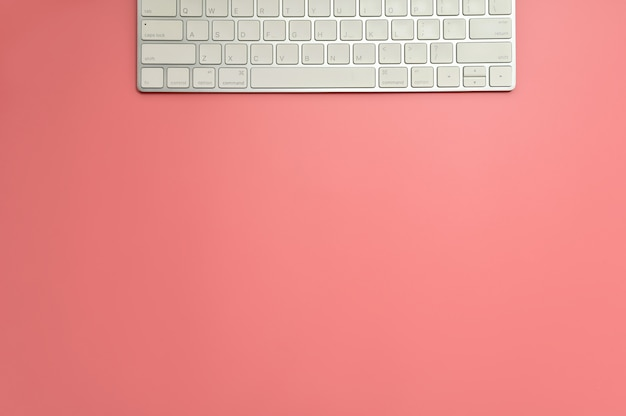 Flat lay, top view office table desk. workspace with keyboard on pink background.