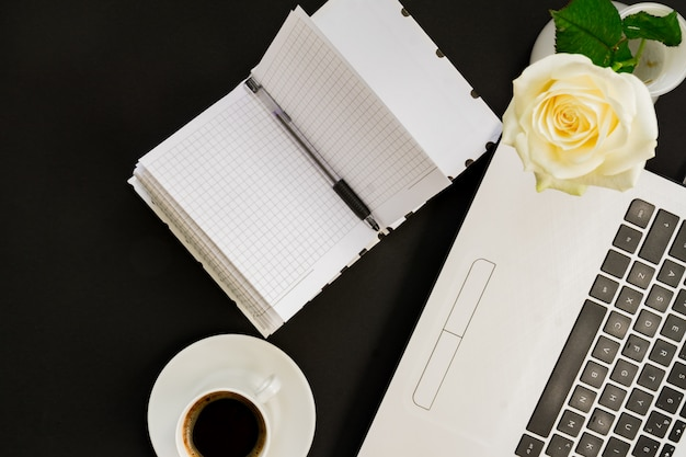 Flat lay, top view office table desk. workspace with laptop, white rose, open diary and coffee mug on black background.
