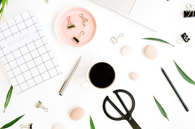 フラットレイ、トップビューオフィステーブルデスク。ノートブック、ラップトップ、椰子の枝、コーヒーカップ、はさみ、白い背景のクリップとワークスペース。