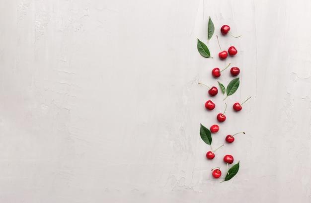 Плоский вид сверху на сером бетонном фоне с ягодами черешни и кубиками льда. свежесть, летний концептуальный минимальный фон. концепция эко, био-фермы и фруктов с копией пространства