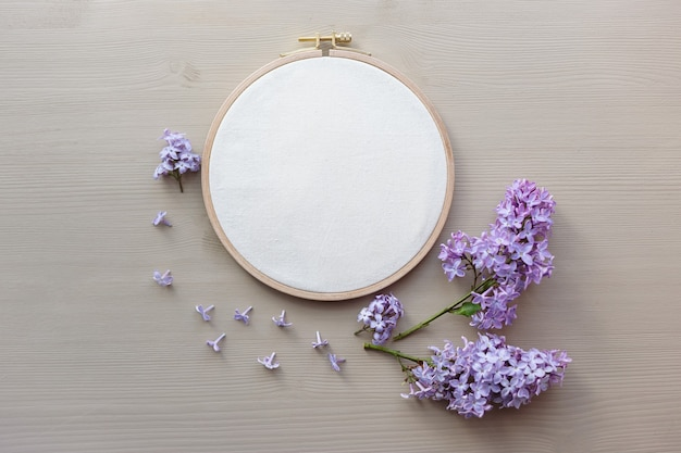 자수 후프와 플라일락 꽃이 있는 모형의 평평한 평면 사진. 세련된 여성스러운 꽃 모형.