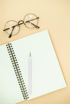 Flat lay top view photo of pencil, glasses and notepad