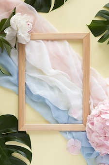 Flat lay and top view of pink and blue scarf and pink summer flowers on pastel yellow background.