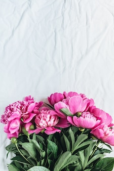 Flat lay, top view of pink peonies flower bouquet on white blanket background