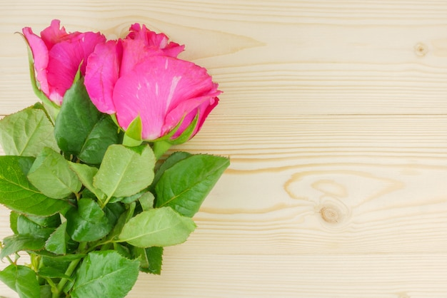 Flat lay, top view pink roses on beige wooden background with copy space