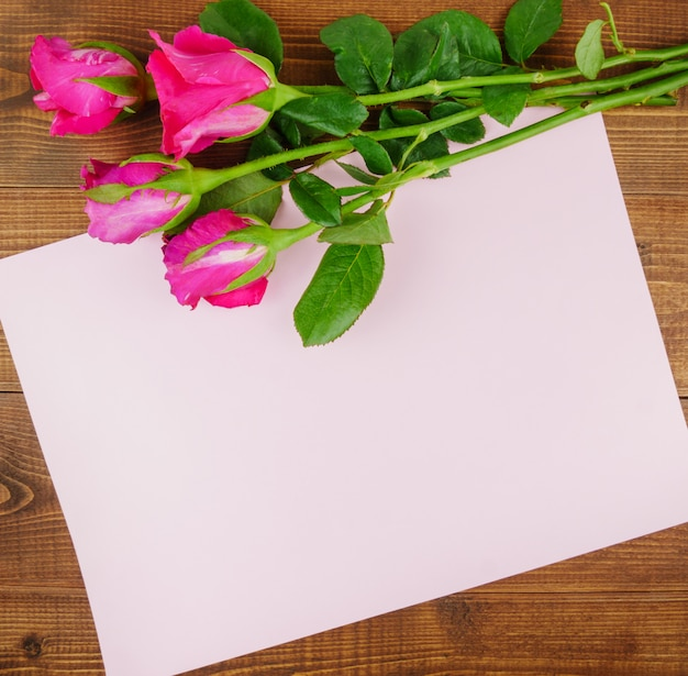 Flat lay, top view pink roses on wooden table with copy space