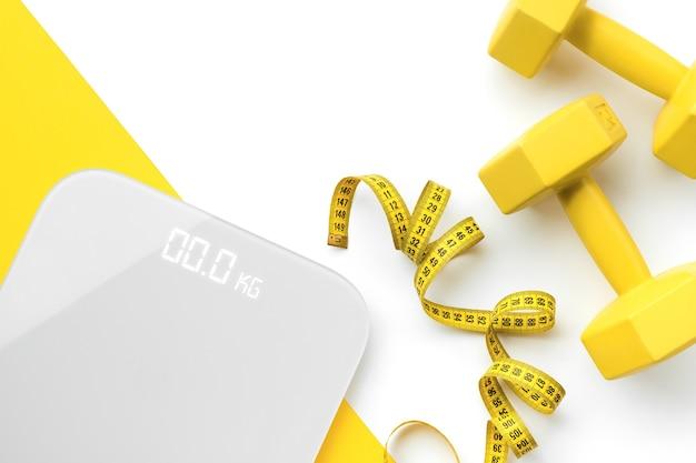 Плоские лежащие сверху весы, гантели и рулетка на бело-желтой поверхности