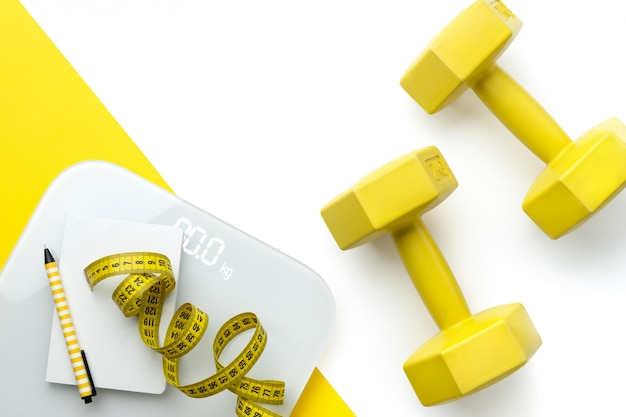 Flat lay top view scales, dumbbell and tape measure on white yellow double background