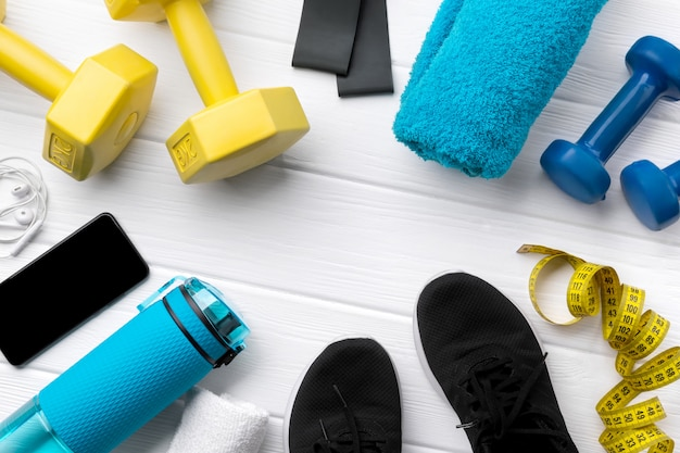 Flat lay top view sport equipments, sneakers and smartphone on white wooden background