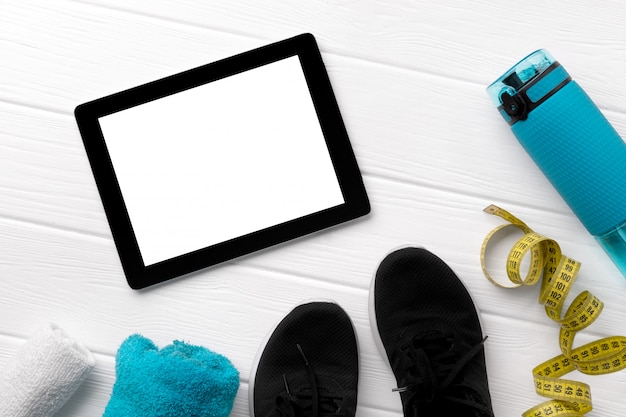 Flat lay top view sport equipments, sneakers and tablet on white wooden background