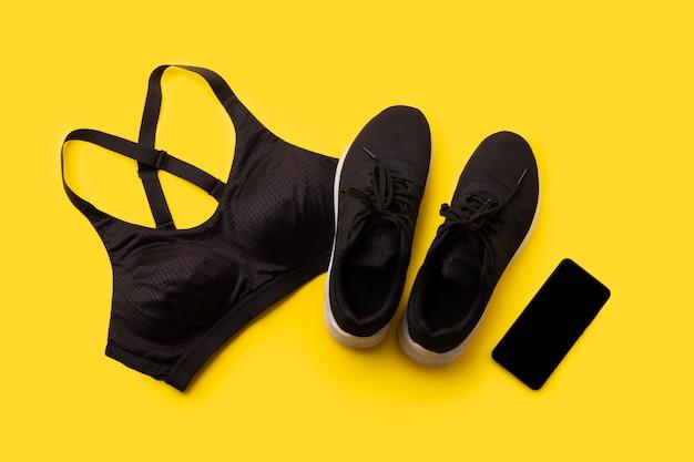 Плоский лежал вид спортивной одежды и смартфон на желтом фоне