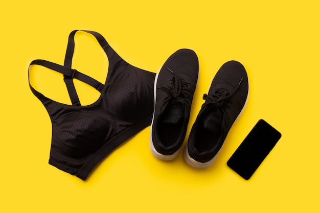 Flat lay top view sportswear and smartphone on yellow background