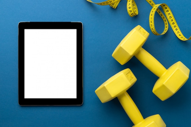 Flat lay top view of tablet with yellow sport equipments on classic blue background