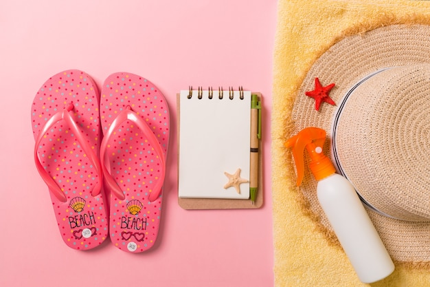 Flat lay, top view travel concept. summer accessories with note paper and seashell on pink background.