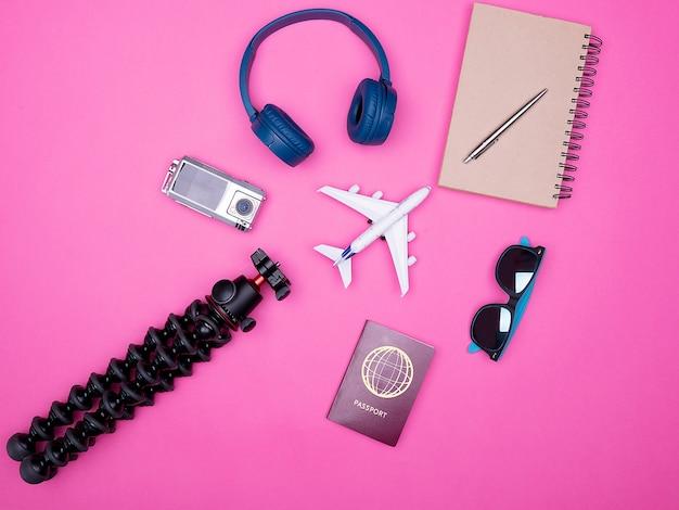 Vista dall'alto piatta degli accessori del fotografo viaggiatore su sfondo rosa. taccuino, passaporto, treppiede, cuffie e occhiali da sole