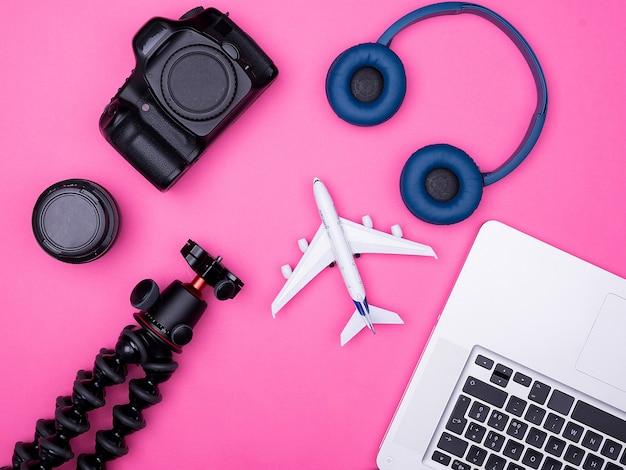 Vista dall'alto piatta degli accessori del fotografo viaggiatore su sfondo rosa. passaporto, taccuino. cuffie,. treppiedi