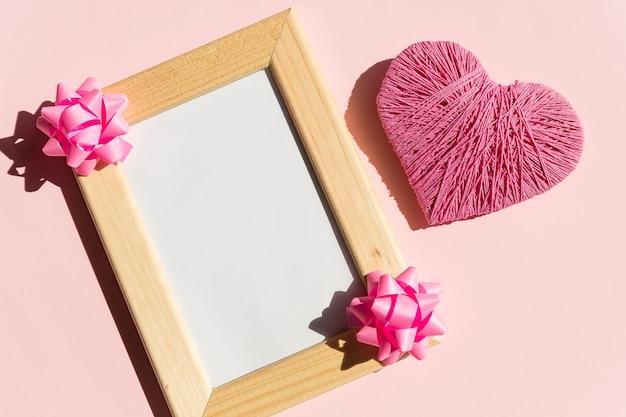 Плоская планировка, вид сверху. концепция дня святого валентина. деревянная рамка, украшенная цветами, копия пространства