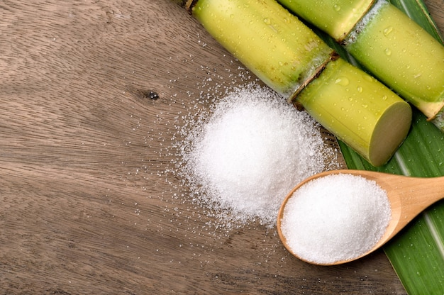 Flat lay (top view) of white sugar with fresh sugar cane on wood background.