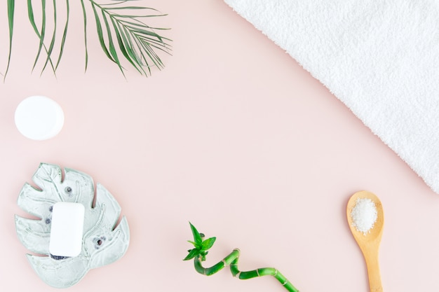 Flat lay and top view of white towel, jar of cream, green palm leaves and bamboo on pastel pink