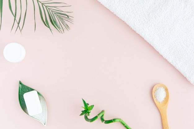 Flat lay and top view of white towel, jar of cream, green palm leaves and bamboo on pastel pink.