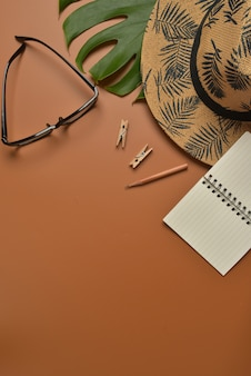 Flat lay, top view workspace on brown background with copy space
