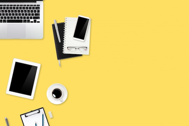 Flat lay or top view workspace office yellow desk with laptop computer, coffee cup and phone using for business background
