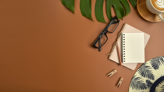 Flat lay, top view workspace with eye glasses, notebook, hat, pencil, green leaf, shoes and coffee cup on brown background.