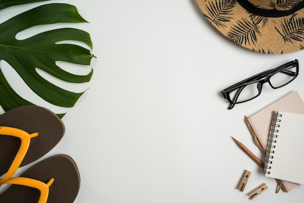 Flat lay, top view workspace with eye glasses, notebook, hat, pencil, green leaf, shoes and coffee cup on white background.