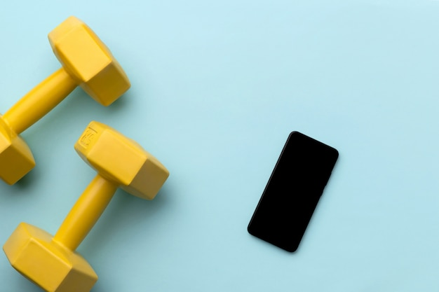 Flat lay top view yellow dumbbells and smartphone on blue background