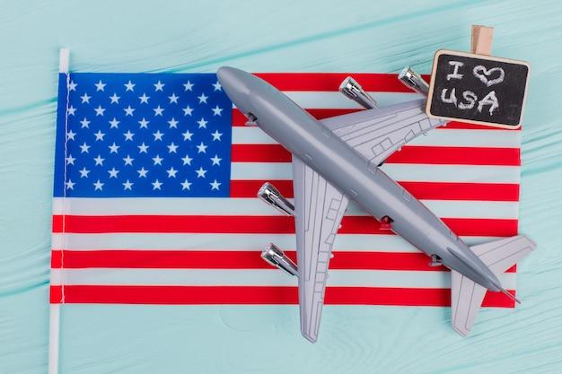 미국 국기에 누워 있는 평평한 장난감 여객기. 미국 여행 컨셉입니다. 미국 개념으로 비행입니다.