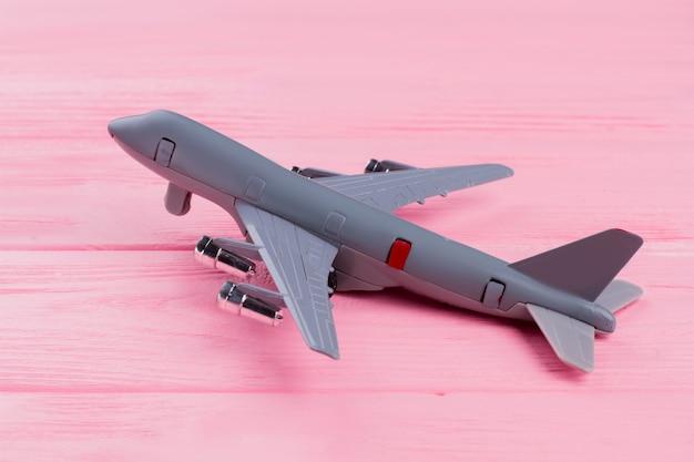 분홍색 나무 배경에 평평한 장난감 비행기. 확대