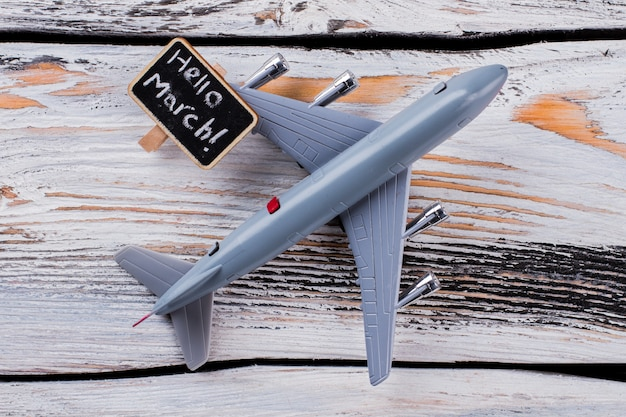Flat lay toy plane and hello march tagline. old white wooden table on the background.