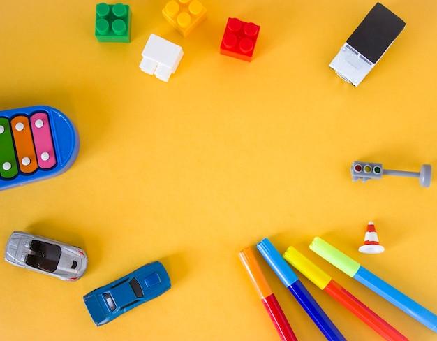 黄色の背景にフラットレイおもちゃ。キューブ、マーカー、木琴、信号機、車