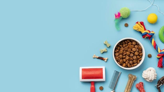 Disposizione piatta di giocattoli con ciotola di cibo e spazzola di pelliccia per cani