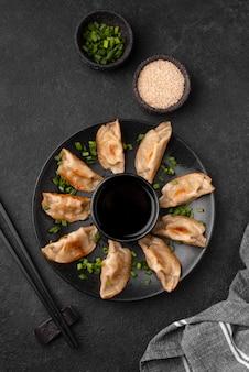 Lay piatto di tradizionali gnocchi asiatici con erbe e bacchette