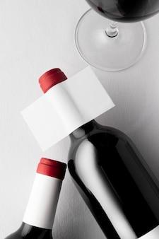 Lay piatto di bottiglie di vino traslucide e bicchieri con etichette vuote