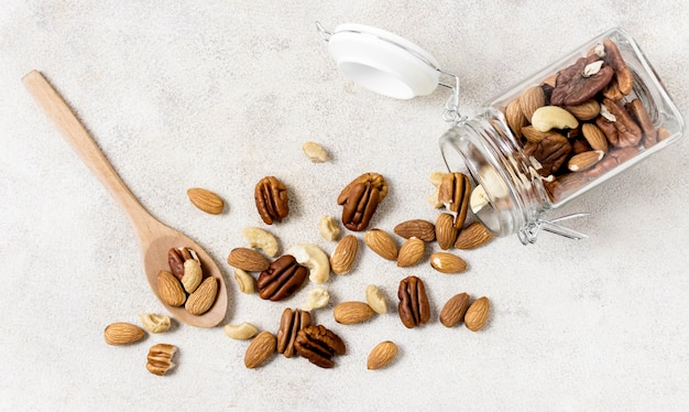 Flat lay of transparent jar with assortment of nuts
