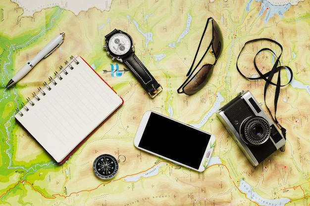Flat lay travel accessories on map background