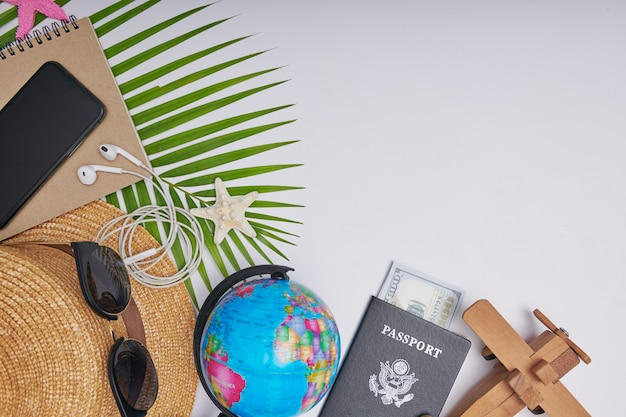 Flat lay travel accessories on white background with palm leaf, camera, hat, passports, money, globe, book, phone, map, and sunglasses. top view, travel or vacation concept. summer background.