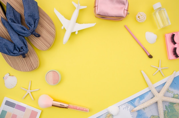 Flat lay of travel accessories with yellow background