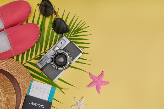 Accessori da viaggio piatti laici su sfondo giallo con foglia di palma, macchina fotografica, scarpe, cappello, passaporti e occhiali da sole. vista dall'alto viaggio o concetto di vacanza. sfondo giallo estivo.