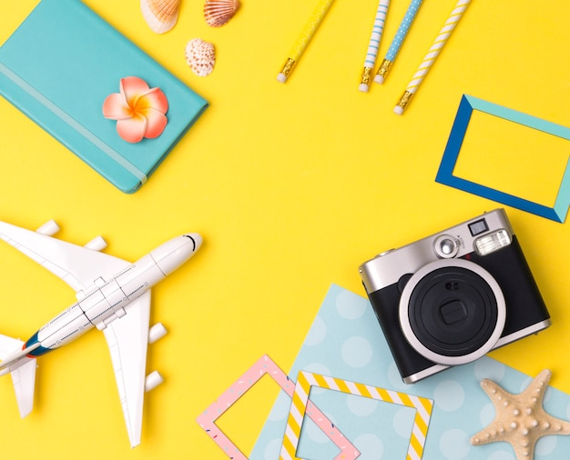 Flat lay travel accessories on yellow table